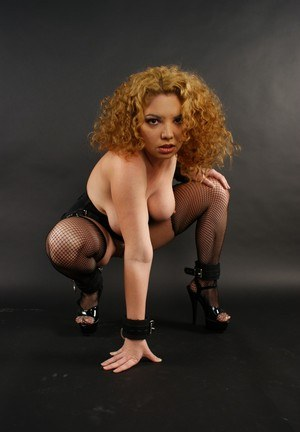 Curly haired chick with curves Kiki Daire shows her tits and ass in dog collar