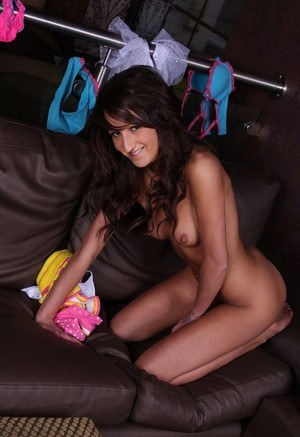 Sassy Danielle in shorts undressing on the couch to pose naked on her knees