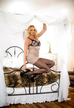 Blonde female bares her big tits as she strips to black stockings and heels