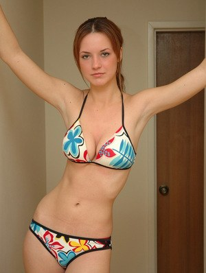 Young solo girl Amy wears a smile while posing non nude in a string bikini