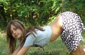Shapely young teen in tiny t-shirt and short skirt posing outdoors