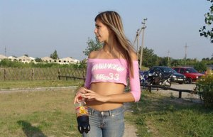 Slender sexy blonde teen in tight jeans  belly shirt posing clothed outdoors