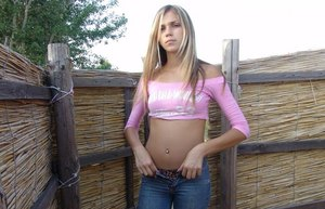 Slender sexy blonde teen in tight jeans & belly shirt posing clothed outdoors