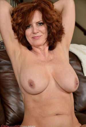 Fun loving hot redhead Andi James frees big breasts to bend nude  spread wide