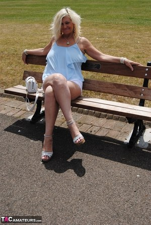 Hot mature Platinum Blonde flashes a hot panty upskirt on a park bench