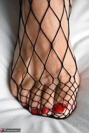 Old woman with short hair and floppy tits dons a strapon in fishnet pantyhose