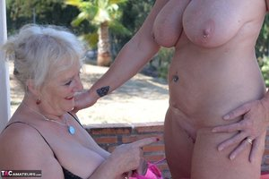 Older lesbian strips her busty blonde lover naked on shaded patio