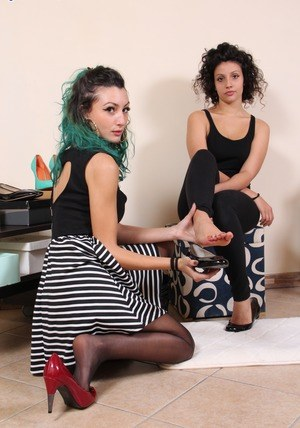 Clothed females takes turns releasing their feet from heels and hose