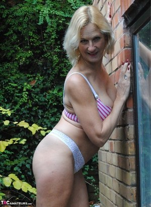 Cute mature MILF Molly sheds shorts in the yard to pose in hot thong panties