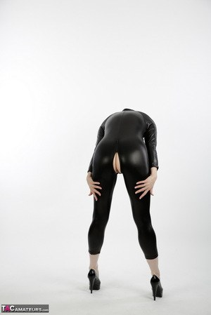 Horny mature in latex catsuit bares saggy boobs  squats to display pussy lips