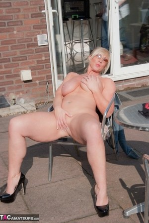 Busty mature wife Melody strips on the patio showing big tits  masturbating