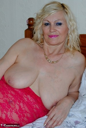Mature sexy Platinum Blonde pulls down red lace dress to expose big saggy tits