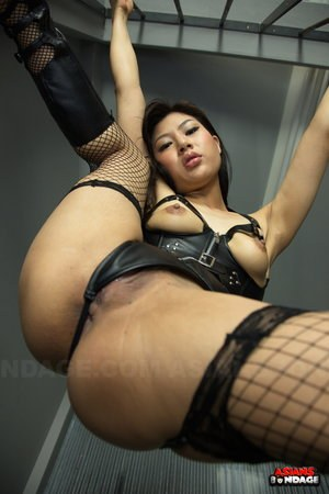 Caged hot Asian Chihiro Asai in leather & fishnet spreading wide behind bars