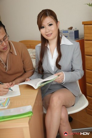 Beautiful Japanese teacher models fully clothed for her admiring student