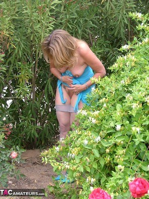Mature Devlynn spreading legs topless in the bushes to pee wearing pantyhose
