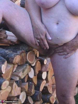 Brazen older granny strips off by the wood pile to show off BBW tits  big ass