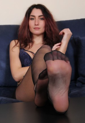 Lingerie model with red hair frees nylon attired feet from ankle strap heels