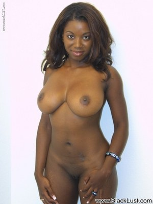 Sexy black girl with a nice smile bares her huge tits before petting her pussy