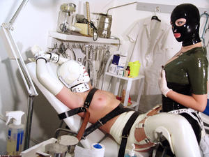 Latex attired lesbians play lezdom games on dental chair