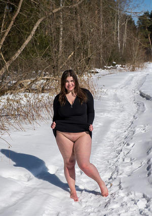 Brunette BBW rids ball gag and ropes while posing nude and barefoot in snow