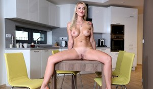 Thin housewife with a tramp stamp rides a big dildo on the kitchen table