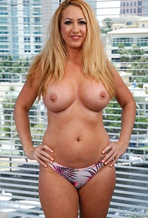 Mature blonde lady Janna Hicks uncorks her big boobs as she strips naked