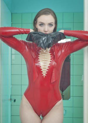Brunette chick in latex bodysuit and high heels dons a rubber mask in bathroom