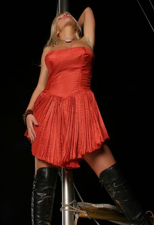 Hot blonde Ines Cudna models in a red dress and OTK boots on sailboat at night