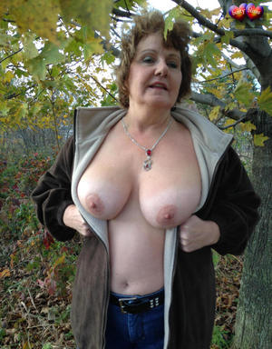 Older woman Busty Bliss exposes her big natural tits under a tree in the fall