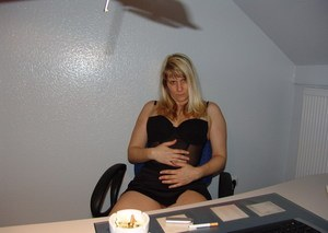 Mature amateur smokes a cigarette before masturbating in office chair