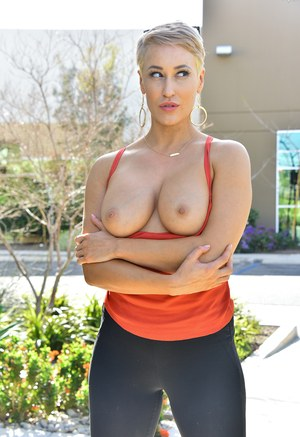 Short haired blonde exposes her nice tits on the sidewalk in black leggings