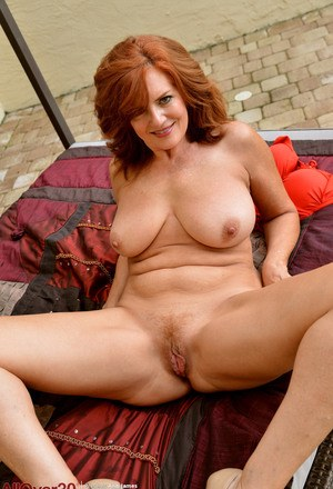 Mature redhead Andi James cups her natural tits while posing nude in heels