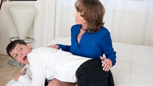 Mature woman Cyndi Sinclair spanks her stepson before jerking his cock