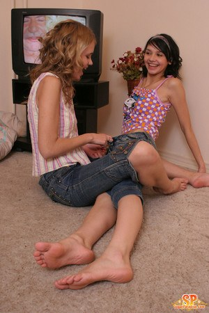 Young looking girls undress each other before tribbing on carpet flooring