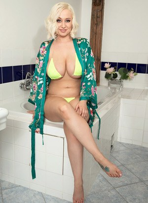 Blonde model Rachael C uncovers her big naturals before stepping into bathtub