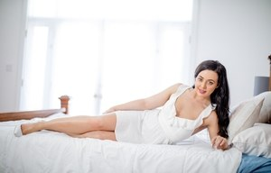 Brunette female slips off white lingerie and underwear atop her bed