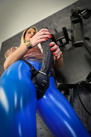 Fully clothed blonde affixes a big black strapon cock to her latex pants