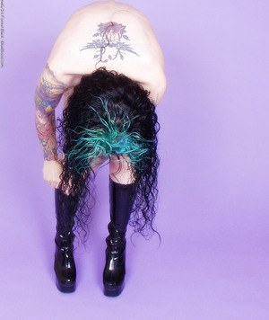 Goth girl with dyed hair and tattoos unzips latex dress to get naked