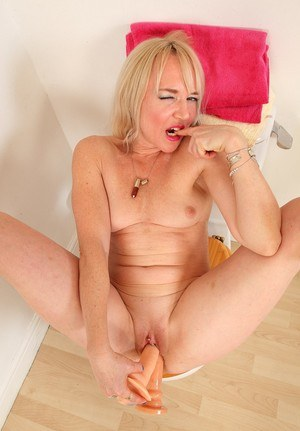 Older blonde MILF rides a dildo on toilet seat after removing pantyhose