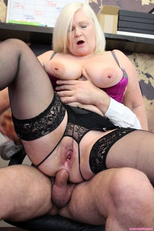 Big boobed granny sports a mouthful of cum after anal sex in her office