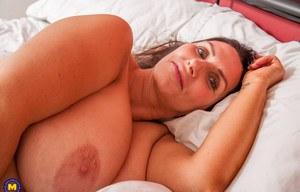 Mature woman unveils her huge boobs by removing her robe in bedfroom