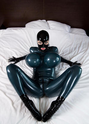 Tall female with huge tits sports the rubber doll look while encased in latex