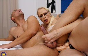 Old blonde woman pegs her submissive lover with her glasses on