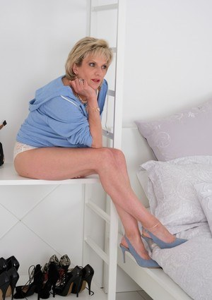 Mature British MILF Lady Sonia strips to bra and panties atop her bed