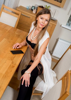 Hot older woman Devina disrobes to black stockings on kitchen table