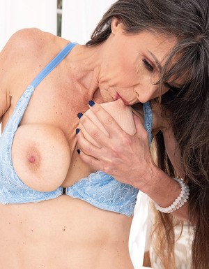 Over 50 lady Beth Sinkati licks a nipple after uncupping her tits in the nude
