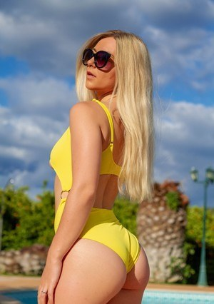 Blonde amateur Elle Hunter works free of her swimsuit for nude poolside poses