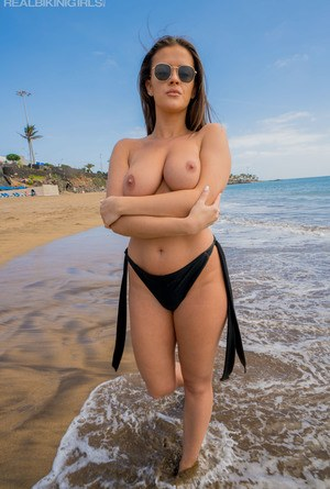 Amateur chick looses her firm breasts from bikini top at the beach in shades